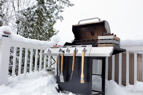 Snow covers a porch with a barbeque's lid open, ready for some winter grilling.