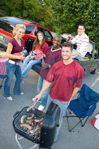 Some young people have a tailgating party going with BBQ food cooking on the grill.